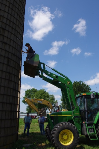 Sons, Nathan and Dallas, attaching a log chain to an old silo that is to be pulled down.
